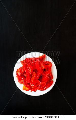 Canned vegetables - Marinated red pepper red peppers on a plate on dark background with copy space. Preserved red sweet chilli peppers