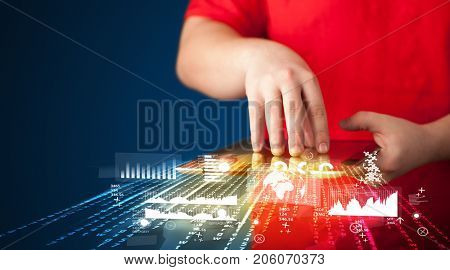 Hand holding touchpad tablet with business market graphs and icons concept on background