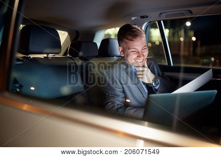 smiling businessman in moving car working overtime on his laptop