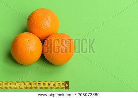 Pattern Made Of Orange Fruits Near Yellow Tape Measure
