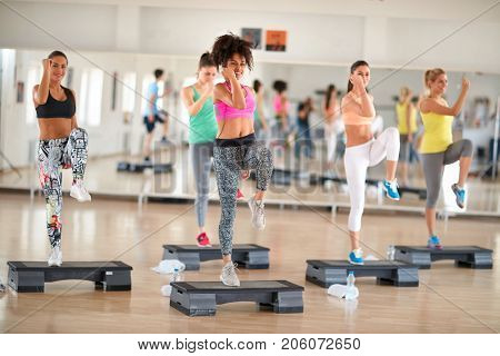 Fitness group training on stepper in colorful sportswear