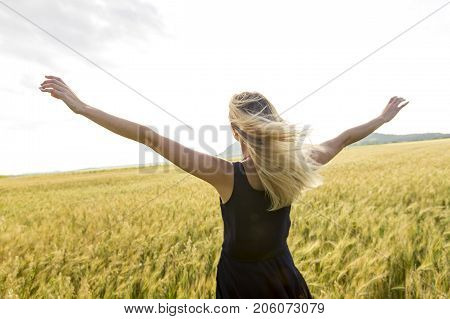 A Happy, satisfied young woman standing in the wheat field.