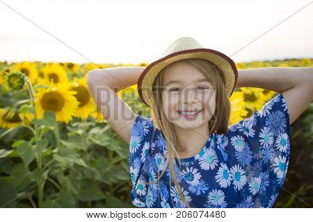 A happy girl on a field of sunflowers on summer sunset