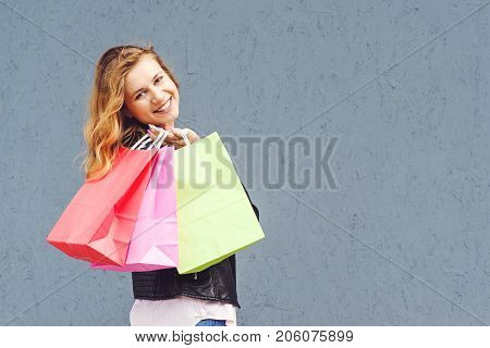 Joyfull casual woman holding shopping bags over grey background.