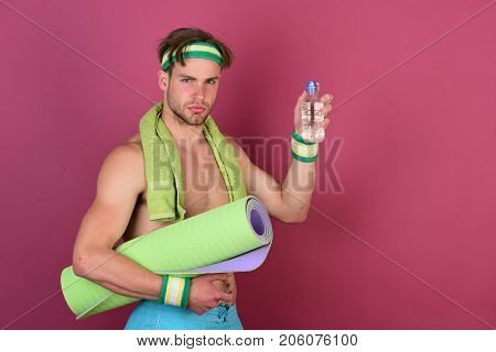 Man With Naked Torso Holds Green Yoga Mat, Purple Background