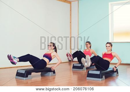 Group of young sport women working out with steppers in a gym.