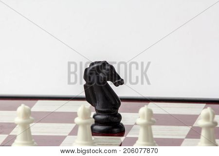 chess black horse in front of white pawns. concept of struggle. Isolated on white background.