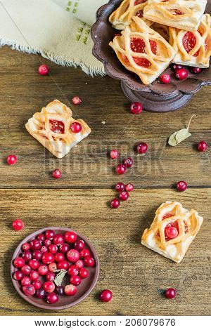 Sweet cranberry dessert. Homemade cookies with jam and fresh ripe cranberries in a small plate on a wooden table.