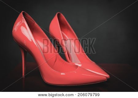 Lacquered shiny pink shoes high heels over grey