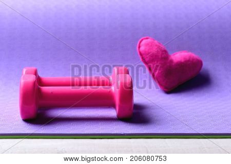 Dumbbells Made Of Pink Plastic Near Heart On Purple Texture