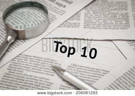 top 10 headline on newspaper with magnifying glass