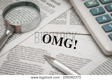 OMG! headline on newspaper background with magnifying glass