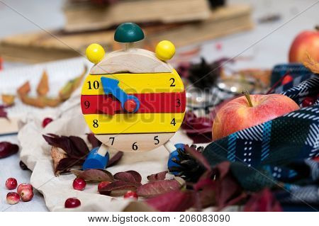 Fall Time Alarm Clock On A Rustic Wooden Table With Colorful Autumn Leaves. With Light Shadow And Sh