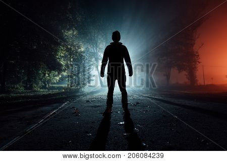 silhouette of an unknown person in a park in the rays of light in an autumn foggy night