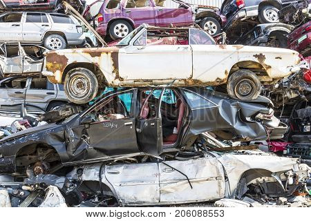 Indianapolis - Circa September 2017: Stacked junk yard clunker cars prepared for crushing to be recycled XII
