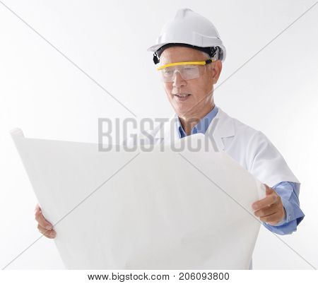 Portrait of Asian contractor with hard hat reading on blueprint, standing isolated on white background.