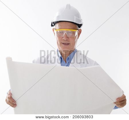 Portrait of Asian contractor with hard helmet reading on blueprint, standing isolated on white background.