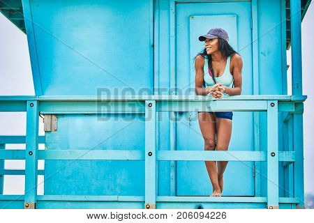 Low angle view of young woman leaning on railing against blue lifeguard hut at beach