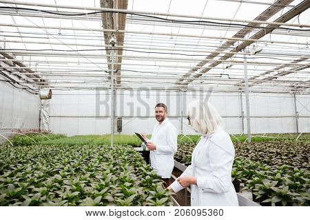 Two biologists working together at a greenhouse