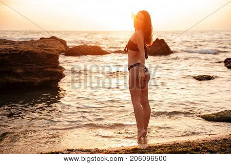 Back view of smiling brunette woman in bikini posing near the sea and looking at the camera