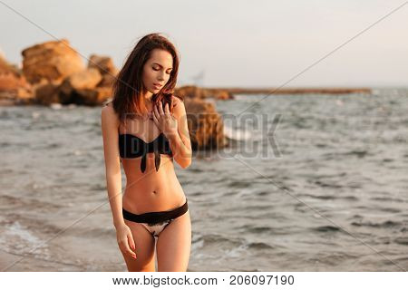 Beauty mystery woman in bikini posing on beach and looking down