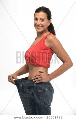 Happy mature woman in old jeans pant after losing weight
