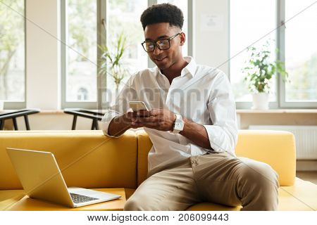 Picture of smiling young african man sitting coworking by laptop computer. Looking aside chatting by phone.