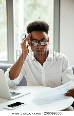 Image of concentrated young african man sitting coworking by laptop computer holding documents. Looking aside.