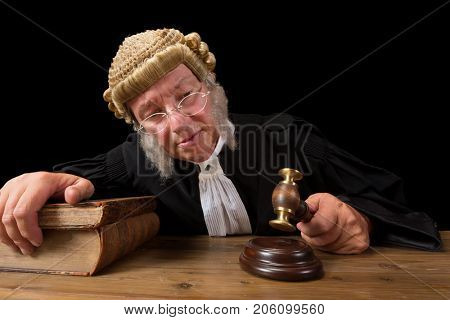 Mature judge with authentic court wig holding a gavel in court