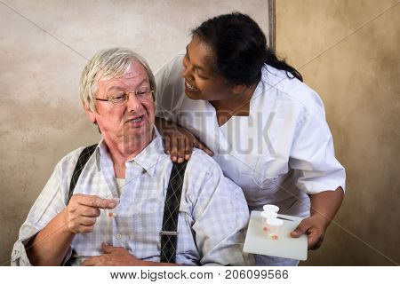 Grumpy old grandpa in nursing home receiving medication by a nurse