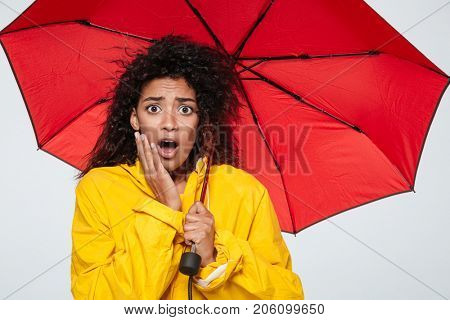 Image of shocked african woman in raincoat hiding under umbrella and looking at the camera over white background