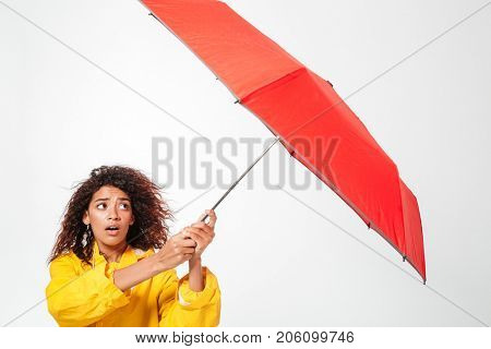 Picture of confused african woman in raincoat holding her umbrella over white background
