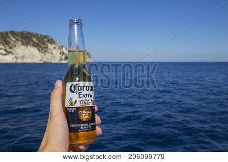 ZAKYNTHOS GREECE - August 1 2017: Corona beer bottle in hand on the sea