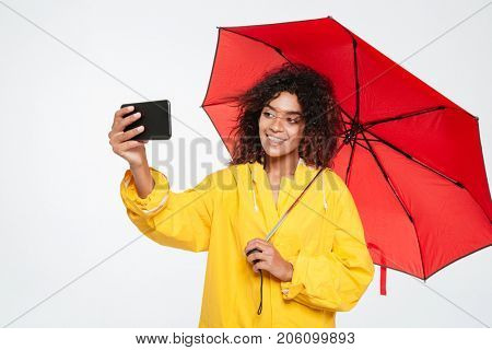 Happy african woman in raincoat hiding under umbrella and making selfie on smartphone over white background
