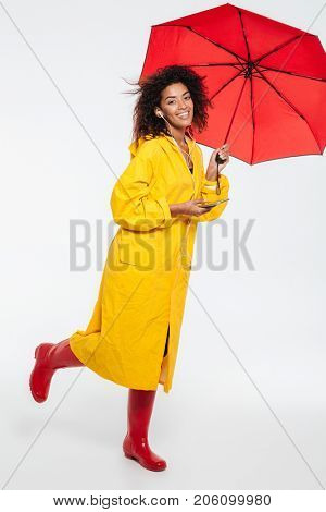 Full length image of happy african woman in raincoat hiding under umbrella and listening music while looking at the camera over white background