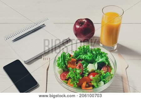 Having lunch in office, pov of vegetable salad on white wooden desk. Salad bowl, apple, orange juice, mobile phone and notepad with pen flat lay. Snack at break time