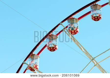 Bright cabs of a ferris wheel on a blue sky background.