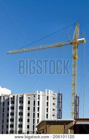 Building A New Multi-storey House Made Of Bricks With The Help Of A Building Crane.