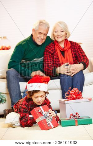 Happy grandparents watching their grandchild opening christmas gifts