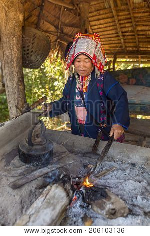 Chiang Rai, Thailand - February 8, 2017: Akha woman with traditional clothes and silver jewelery working in smithy, Northern Thailand