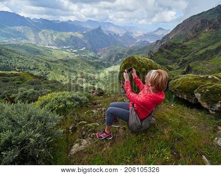 Young woman tourist with backpack sitting on cliff's edge and taking photos