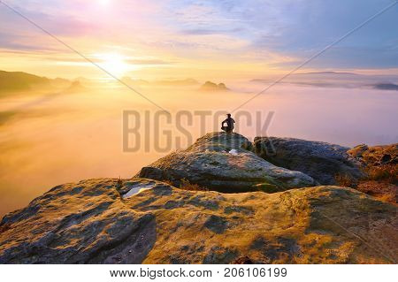 Hiker In Squatting Position On Peak Of Rock And Watching Into Colorful Mist And Fog In Morning Valle