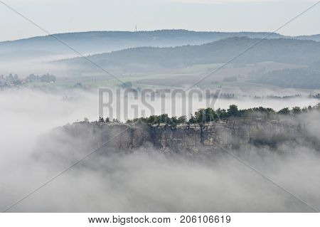 Autumn Landscape. Morning View Over Sandstone Cliff Into Deep Misty Valley. Sandstone Peaks