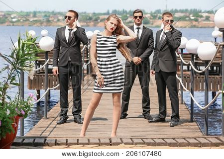 Young celebrity with bodyguards outdoors