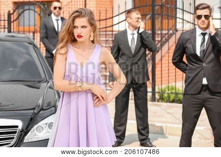 Young celebrity with bodyguards near car outdoors