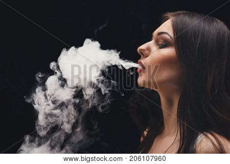 Woman vaping electronic cigarette with smoke on black background closeup. Brunette girl blowing a cloud of smoke on black background. Nicotine free smoking and vapor concept, copy space