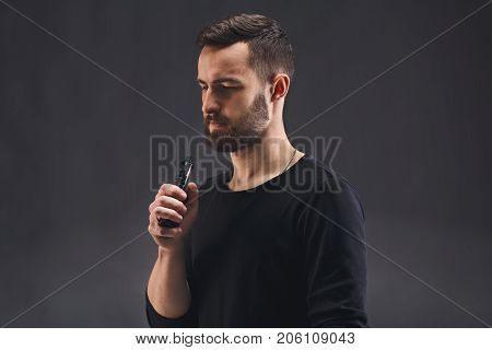 Man with vape at black studio background closeup. Young bearded guy smoking e-cigarette to quit tobacco. Vapor and alternative nicotine free smoking concept, copy space