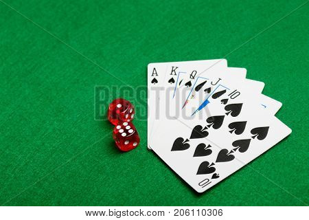 Playing cards flush and red dice on green casino desk  background