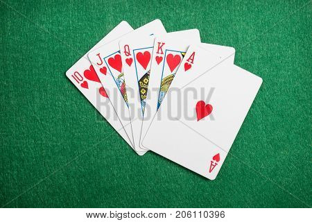 Playing cards flush  on green casino desk  background
