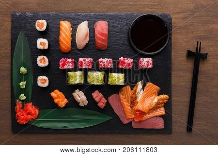 Japanese restaurant, sushi roll platter top view on black rustic wood background and black slate plates. Set with chopsticks, ginger, soy, wasabi.
